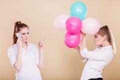 Dos muchachas con el teléfono móvil y los globos Fotos de archivo libres de regalías