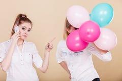 Dos muchachas con el teléfono móvil y los globos Imagen de archivo