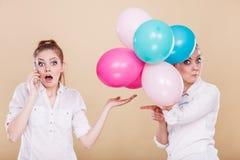 Dos muchachas con el teléfono móvil y los globos Foto de archivo libre de regalías