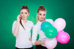Dos muchachas con el teléfono móvil y los globos Foto de archivo