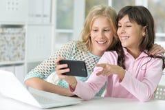 Dos muchachas con el teléfono y el ordenador portátil Foto de archivo