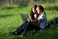 Dos muchachas con la computadora portátil Fotos de archivo libres de regalías