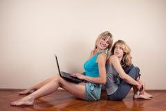 Dos muchachas con la computadora portátil Imagen de archivo libre de regalías