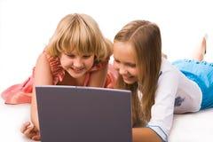 Dos muchachas con la computadora portátil imagen de archivo