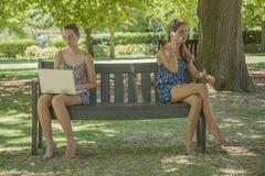 Dos muchachas con la computadora portátil y el teléfono elegante Fotografía de archivo libre de regalías
