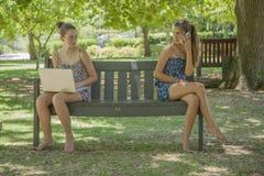 Dos muchachas con la computadora portátil y el teléfono elegante al aire libre Fotografía de archivo libre de regalías