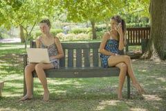 Dos muchachas con la computadora portátil y el teléfono elegante al aire libre Imagen de archivo