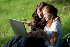 Dos muchachas con la computadora portátil Foto de archivo