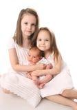 Dos muchachas con la hermana recién nacida Imagen de archivo libre de regalías