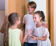 Dos muchachas con la reunión del adolescente en entrada Fotografía de archivo