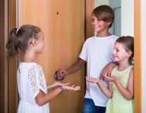 Dos muchachas con la reunión del adolescente en entrada Fotografía de archivo libre de regalías