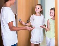 Dos muchachas con la reunión del adolescente en entrada Imagen de archivo libre de regalías