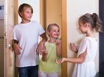 Dos muchachas con la reunión del adolescente en entrada Foto de archivo libre de regalías