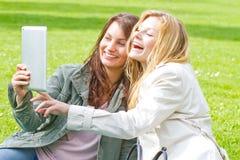 Dos muchachas con la tableta Imagenes de archivo