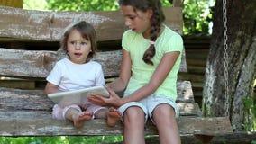 Dos muchachas con la tableta se sientan en el banco del oscilación metrajes