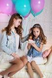 Dos muchachas con la torta y los globos de cumpleaños Imágenes de archivo libres de regalías
