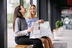 Dos muchachas con las compras que se sientan en un banco en la alameda Imagen de archivo libre de regalías