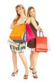 Dos muchachas con los bolsos - compras de la comparación. ¡Venta! Imágenes de archivo libres de regalías