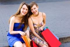 Dos muchachas con los bolsos de compras Fotografía de archivo libre de regalías