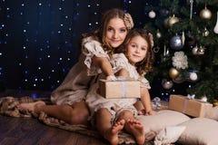Dos muchachas con los regalos de la Navidad en casa Imagen de archivo libre de regalías