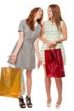 Dos muchachas con los regalos después de hacer compras Imagen de archivo libre de regalías