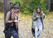 Dos muchachas con los teléfonos Fotografía de archivo libre de regalías