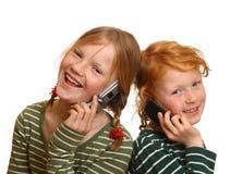 Dos muchachas con los teléfonos celulares Imágenes de archivo libres de regalías