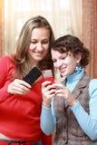 Dos muchachas con los teléfonos móviles Fotografía de archivo libre de regalías