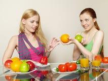 Dos muchachas con los vehículos y la fruta Imágenes de archivo libres de regalías