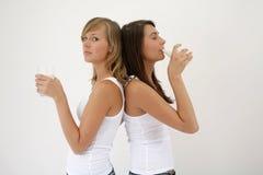 Dos muchachas con los vidrios de leche Fotografía de archivo