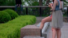 Dos muchachas con smartphones en el parque almacen de metraje de vídeo