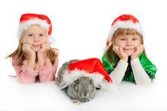 Dos muchachas con un conejo en casquillos rojos de Santy Fotos de archivo