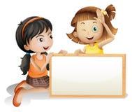 Dos muchachas con un tablero blanco en blanco Imagen de archivo libre de regalías
