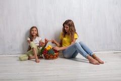 Dos muchachas con una cesta de consumición sana de la fruta fresca foto de archivo