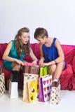 Dos muchachas consideran y se muestran compras Imágenes de archivo libres de regalías