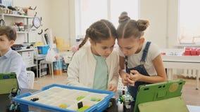 Dos muchachas construyen el robot plástico usando la instrucción del ipad en la cámara lenta de la lección almacen de video