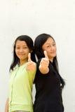 Dos muchachas dan los pulgares para arriba Fotos de archivo libres de regalías
