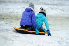 Dos muchachas de adolescentes juntas se mueven abajo desde una colina en el trineo Fotografía de archivo libre de regalías