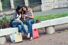 Dos muchachas de compras en parque con un teléfono móvil Fotos de archivo libres de regalías