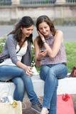 Dos muchachas de compras en parque con un teléfono móvil Imágenes de archivo libres de regalías