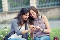 Dos muchachas de compras en parque con un teléfono móvil Imagen de archivo