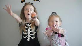 Dos muchachas de Cutie en disfraces de Halloween se est?n divirtiendo junto Trajes divertidos Aislado metrajes