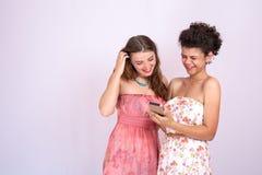 Dos muchachas de diversas razas obran recíprocamente y discuten la información en el smartphone Internet, comunicación Imágenes de archivo libres de regalías