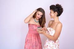 Dos muchachas de diversas razas que se divierten con el smrtfonom Internet, comunicación Imágenes de archivo libres de regalías