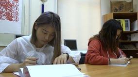 Dos muchachas de estudiantes asiáticos estudian en la sala de clase usando los cuadernos almacen de metraje de vídeo