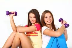 Dos muchachas de la aptitud con las pesas de gimnasia Imágenes de archivo libres de regalías