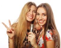 Dos muchachas de la belleza con un micrófono que cantan y que se divierten Fotos de archivo