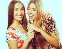 Dos muchachas de la belleza con un micrófono que cantan y que se divierten Foto de archivo libre de regalías