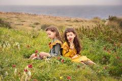Dos muchachas de la hermana en vintage pasado de moda visten las flores el oler que se sientan en una meseta cerca del mar tempes foto de archivo libre de regalías