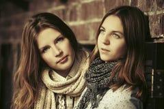 Dos muchachas de la moda de los jóvenes al lado de la pared de ladrillo Imágenes de archivo libres de regalías